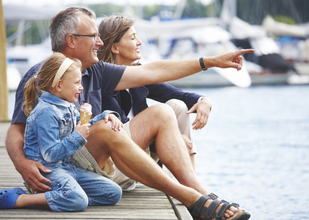 Happy Grandparents sitting with their granddaughter on a pier, pointing out at the boats - copyspace